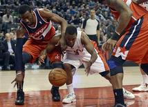 Toronto Raptors Kyle Lowry (3) is fouled by Washington Wizards John Wall (2) during the first half of their NBA basketball game in Toronto, February 25, 2013. REUTERS/Aaron Harris