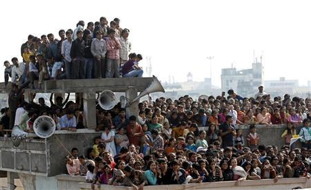 People stand on top of a house in Raipur January 29, 2012. REUTERS/Amit Dave/Files