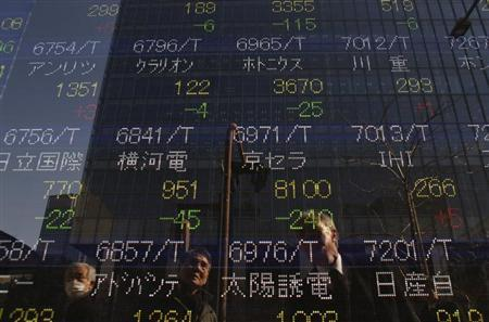 Passers-by are reflected on a stock quotation board outside a brokerage in Tokyo February 26, 2013. Japan's Nikkei average stumbled 2.3 percent on Tuesday, its biggest one-day drop in more than a month, as concerns grew that inconclusive elections in Italy could reignite the euro zone debt crisis. REUTERS/Issei Kato (JAPAN - Tags: BUSINESS) - RTR3EAPU