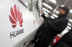 Люди рассматривают мобильные телефоны на стенде Huawei в Шанхае 22 января 2013 года. Китайские компании Huawei и ZTE всерьез настроились посоперничать с Apple и Samsung, и представили конкурентов популярным девайсам iPhone и Galaxy. REUTERS/Carlos Barria