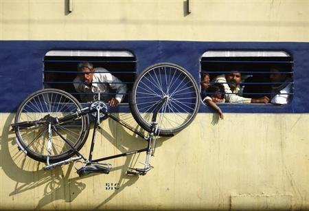 A bicycle hangs from the window of a train at Parsha Bazar railway station in Bihar October 27, 2012. REUTERS/Navesh Chitrakar