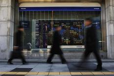 Passanti davanti a un display che mostra l'andamento degli indici di borsa a Tokyo. REUTERS/Yuya Shino