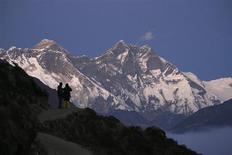 Путешественники смотрят на Эверест в Непале 3 декабря 2009 года. Непальская альпинистка Чхурим Шерпа признана первой женщиной, поднявшейся на высочайшую вершину планеты Эверест дважды за неделю, подтвердили составители Книги рекордов Гиннесса. REUTERS/Gopal Chitrakar