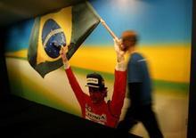 Un par de guantes de competición utilizados por el fallecido piloto Ayrton Senna en la temporada 1991, cuando ganó su tercer título de Fórmula Uno, se vendieron el lunes por 22.000 libras (unos 25.600 euros) en una subasta benéfica. En la imagen de archivo, un hombre pasa junto a una foto gigante de Ayrton Senna, el 21 de octubre de 2004. REUTERS/Bruno Domingos