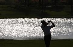 Philippines Juvic Pagunsan is silhouetted against a lake while hitting from the 17th hole fairway during third round of the Volvo Masters of Asia golf tournament, the Asian Tour's season-ending finale, in Bangkok December 8, 2007. REUTERS/Adrees Latif