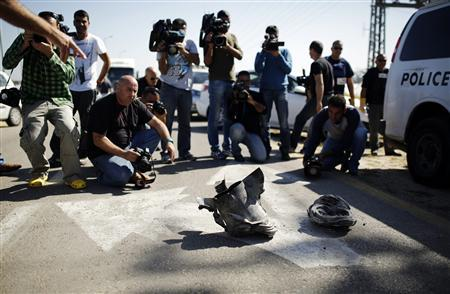 Members of the media photograph the remains of a rocket, displayed by Israeli explosives experts, at Kibbutz Zikim near Ashkelon February 26, 2013. The rocket, fired from Gaza, exploded in Israel on Tuesday, the first such attack since a November truce and an apparent show of solidarity with West Bank protests after the death of a Palestinian in an Israeli jail. REUTERS/Amir Cohen