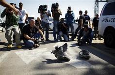 Mídia fotografa os restos de um foguete, mostrados por especialistas em explosivos israelenses, no kibbutz Zikim, em Israel. Um foguete lançado da Faixa de Gaza explodiu no sul de Israel, no primeiro ataque deste tipo realizado por militantes islâmicos do Hamas desde que uma trégua encerrou uma série de confrontos entre as fronteiras em novembro. 26/02/2013 REUTERS/Amir Cohen