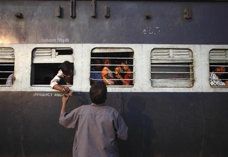 A vendor sells tea to commuters inside the train in Uttar Pradesh October 25, 2012. REUTERS/Navesh Chitrakar/Files