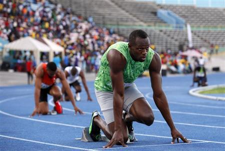 Jamaican runner Usain Bolt takes his mark before running in the men's 400m race of the Camperdown Classic, an annual track event in its ninth year, in Kingston February 9, 2013. REUTERS/Gilbert Bellamy