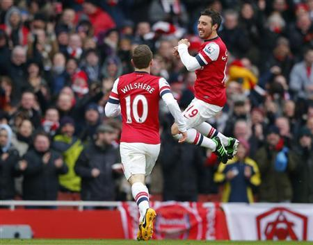 Santi Cazorla (R) of Arsenal celebrates after scoring his team's first goal against Aston Villa during their English Premier League soccer match at the Emirates Stadium in London February 23, 2013. REUTERS/Andrew Winning