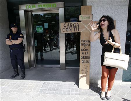 A woman shouts outside a Bankia bank branch as policemen stand guard during an anti-eviction protest in Madrid in this June 1, 2012 file photo. REUTERS/Andrea Comas/Files
