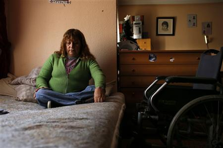 Marcheline Rosero, 45, disabled from the effects of polio as a child in Ecuador, sits on her bed in her flat in Madrid December 17, 2012. REUTERS/Juan Medina