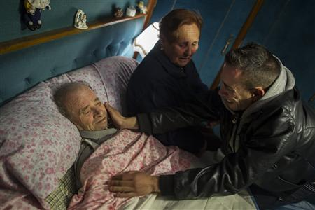 Vicente Torres (L) is comforted by his grandson Jonathan as his sister-in-law Maria looks on, after learning that his eviction was suspended until May 3, in Madrid in this April 18, 2012 file photo. Vicente, a severely ill 74-year-old pensioner, faced an eviction after falling to pay mortgage as guarantor of his son, who has already been evicted from his home. For more than a century, Spanish law has determined that if a person borrows money to buy a home, they can only be freed of the debt when it is repaid. Even in death, the debt is not cancelled. As the country enters another year of recession, calls are mounting for the system to be relaxed. But the banks worry this would damage their access to funds. Picture taken April 18, 2012. To match Insight SPAIN/MORTGAGE-REFORM REUTERS/Juan Medina/Files (SPAIN - Tags: BUSINESS POLITICS REAL ESTATE)