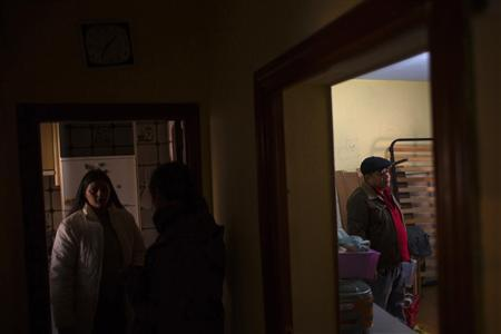 Jenifer Martinez (L) of Spain and Jorge Sanchez of Colombia wait for the judicial commission, before learning that their family's eviction has been suspended, in their home in Madrid December 3, 2012. For more than a century, Spanish law has determined that if a person borrows money to buy a home, they can only be freed of the debt when it is repaid. Even in death, the debt is not cancelled. As the country enters another year of recession, calls are mounting for the system to be relaxed. But the banks worry this would damage their access to funds. Picture taken December 3, 2012. To match Insight SPAIN/MORTGAGE-REFORM REUTERS/Juan Medina (SPAIN - Tags: BUSINESS POLITICS REAL ESTATE)