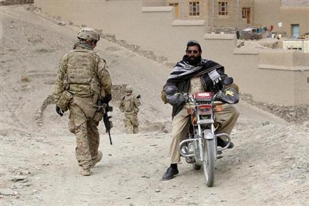 An Afghan resident drives past U.S. soldiers of the 2nd Platoon C Company 9th Engineer Battalion COP Dash Towp patrolling during an overall security and disruption insurgency mission in Wardak province, eastern Afghanistan November 17, 2011. REUTERS/Umit Bektas/Files