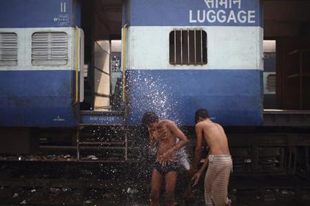 A boy washes using a pipe that supplies water to trains at Old Delhi Railway Station in Delhi November 13, 2012. REUTERS/Navesh Chitrakar
