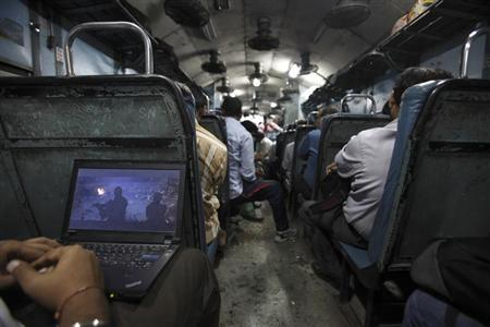 A man watches a film on his laptop as the train heads toward Agra from Delhi October 23, 2012. REUTERS/Navesh Chitrakar/Files