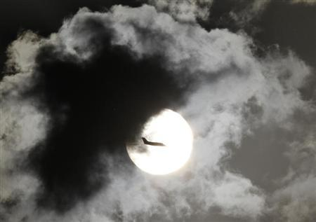 A passenger aircraft is silhouetted against the rising sun after taking off from New Delhi's Indira Gandhi International Airport April 3, 2012. IREUTERS/B Mathur