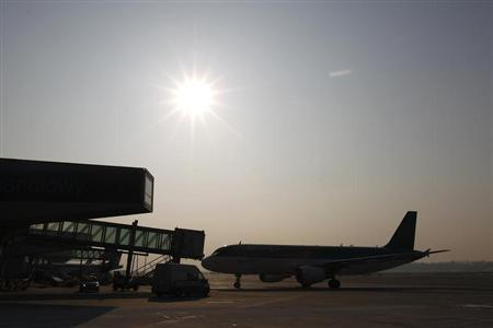 An Aer Lingus plane docks at the gate at the Chopin International Airport in Warsaw February 6, 2012. REUTERS/Peter Andrews
