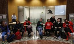 Durante más de un siglo, el derecho español decreta que si una persona pide un préstamo para comprar una vivienda, sólo puede ser liberado de la deuda cuando devuelve el capital. Ni la muerte cancela la deuda. En la imagen de archivo, un empleado de Bankia habla por teléfono mientras miembros de la Plataforma de Afectados por la Hipoteca (PAH) protesta dentro de la oficina de la caja nacionalizada, en Madrid, el 26 de octubre de 2012. REUTERS/Andrea Comas