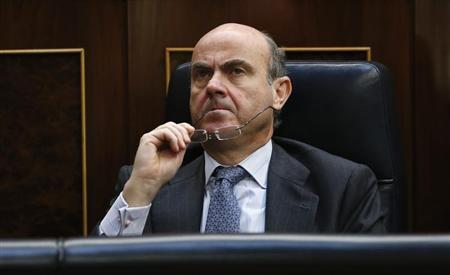 Spain's Economy Minister Luis de Guindos bites his glasses as he attends the State of the Nation debate at Parliament in Madrid February 20, 2013. REUTERS/Sergio Perez