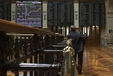 El Ibex-35 bajaba con fuerza a la media sesión del martes, aunque cotizaba por encima de los mínimos niveles de la mañana, con órdenes de venta por parte del dinero más especulativo y cortoplacista en un clima de preocupación política tras las elecciones en Italia. En la imagen, un operador observa un panel electrónico en la Bolsa de Madrid, el 3 de agosto de 2012. REUTERS/Juan Medina