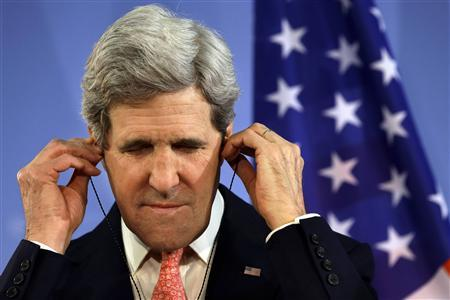 U.S. Secretary of State John Kerry adjusts his translation earphones while listening to German Foreign Minister Guido Westerwelle (unseen) at a news conference at the Foreign Ministry in Berlin February 26, 2013. Berlin is the second stop in Kerry's first trip overseas as secretary. REUTERS/Jacquelyn Martin/Pool (GERMANY - Tags: POLITICS)