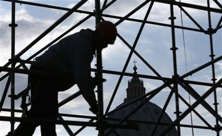 A worker sets up a structure for TV media in front of St. Peter's Square in Rome February 26, 2013. REUTERS/Alessandro Bianchi