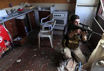 A fighter from the Sadik unit of Free Syrian Army's Tahrir al Sham brigade fires his Steyr AUG rifle from inside a house during heavy fighting in Mleha suburb of Damascus, in this January 22, 2013 file photograph. REUTERS/Goran Tomasevic/Files