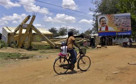 A woman with her child rides her cycle past a destroyed building and a billboard featuring a picture of Sri Lankan President Mahinda Rajapakse in war-hit Kilinochchi town on September 7, 2011.REUTERS/ALERTNET/Nita Bhalla/Files