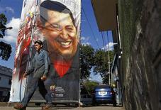 Una persona camina frente a un afiche con la imagen del presidente de Venezuela, Hugo Chávez, instalado a las afueras del hospital militar en donde se encuentra en Caracas, feb 25 2013. La mayoría de los venezolanos confía en que el presidente Hugo Chávez se curará del cáncer y volverá a gobernar, pese a que no ha sido escuchado ni visto en público desde inicios de diciembre, cuando se sometió a su cuarta cirugía por la enfermedad, reveló el martes un sondeo. REUTERS/Carlos Garcia Rawlins
