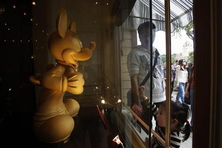 A young visitor looks at a 200-tael pure gold sculpture in the shape of Mickey Mouse being displayed inside a jewellery store at Hong Kong Disneyland February 18, 2013. REUTERS/Bobby Yip