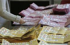 Uma autoridade eleitoral corta cédulas em uma seção eleitoral em Roma, Itália. Os partidos políticos italianos buscam nesta terça-feira algum tipo de acordo, depois de uma eleição em que nenhum deles conseguiu maioria parlamentar, abrindo a possibilidade de uma prolongada instabilidade e de uma nova crise financeira europeia. 25/02/2013 REUTERS/Yara Nardi