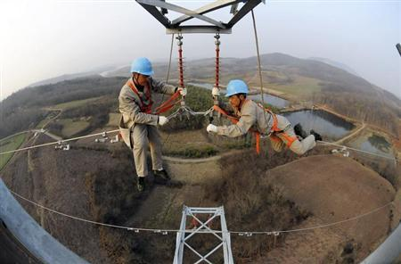 Workers check on electricity pylon situated amid farmlands in Chuzhou, Anhui province, February 5, 2013. REUTERS/China Daily