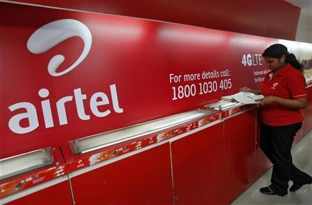An employee checks a customers' feedback book next to a Bharti Airtel logo inside its shop in Kolkata May 2, 2012. REUTERS/Rupak De Chowdhuri/Files