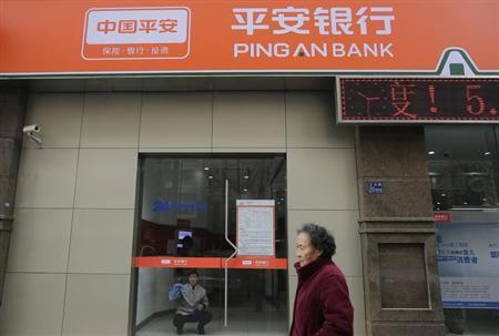 A cleaner wipes a glass door as a woman walks past a Ping An Bank branch in Wuhan, Hubei province, January 11, 2013. REUTERS/Stringer