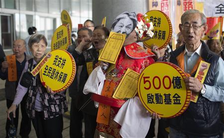 A protester dressed as the Chinese God of Fortune demonstrates, along with other protesters, to demand that the retirement scheme are protected outside the Legislative Council in Hong Kong February 27, 2013 before Hong Kong's Financial Secretary John Tsang gives his annual budget report. REUTERS/Tyrone Siu