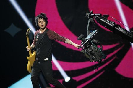 Green Day lead vocalist and guitarist Billie Joe Armstrong grabs a camera during the 2012 iHeart Radio Music Festival at the MGM Grand Garden Arena in Las Vegas, Nevada September 21, 2012. REUTERS/Steve Marcus/Files
