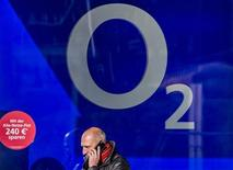 A man speaks on the phone as he walks past the O2 flagship store in Berlin October 16, 2012. REUTERS/Thomas Peter (GERMANY - Tags: BUSINESS TELECOMS) - RTR3977I
