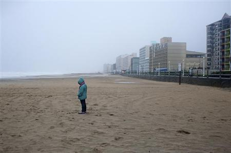 A beachgoer along the oceanfront observes the effects of high wind and heavy rain as Hurricane Sandy begins to arrive in Virginia Beach, Virginia, October 28, 2012. REUTERS/Rich-Joseph Facun