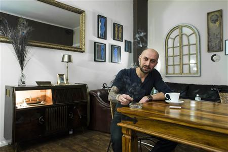 Dimitri Nikolaev Grigorov of Spain poses for a picture in his cafe in the Friedrichshain district of Berlin, January 7, 2013. REUTERS/Thomas Peter