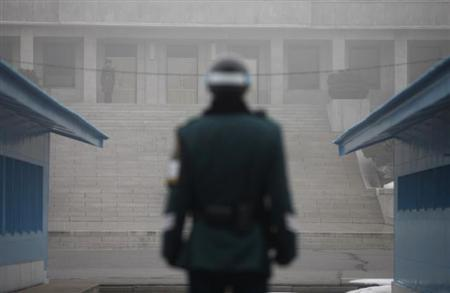 A North Korean soldier (top L) looks south on the North side, as a South Korean soldier stands guard in the ''Truce Village'' of Panmunjom in the demilitarised zone, which separates the two Koreas, in Paju, north of Seoul February 27, 2013. REUTERS/Kim Hong-Ji
