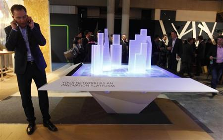A visitor talks on his mobile phone during the Mobile World Congress in Barcelona February 26, 2013. REUTERS/Gustau Nacarino