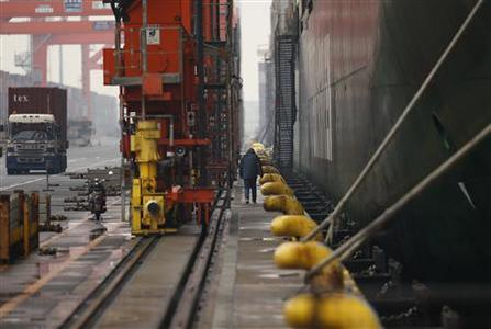 A man walks between a a container ship and its landing pier at a port in Tokyo February 27, 2013. Japanese Prime Minister Shinzo Abe appears poised to raise the curtain on Act Three of his ''Abenomics'' drama with a decision to join talks on a U.S.-led free trade pact, seen by some as a test of his appetite for vital economic reform. REUTERS/Yuya Shino
