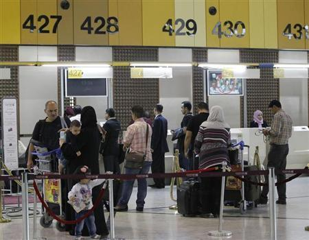 Travellers stand in line with their luggage at Baghdad International Airport October 25, 2012. REUTERS/Mohammed Ameen