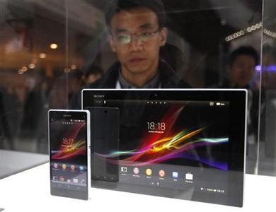 A visitor looks at the new Sony Xperia Z phone and tablet through a glass window during the Mobile World Congress in Barcelona February 25, 2013. The GSMA Mobile World Congress, representing the interests of the worldwide mobile communications industry, takes place from February 25 to 28 in Barcelona.   REUTERS/Gustau Nacarino