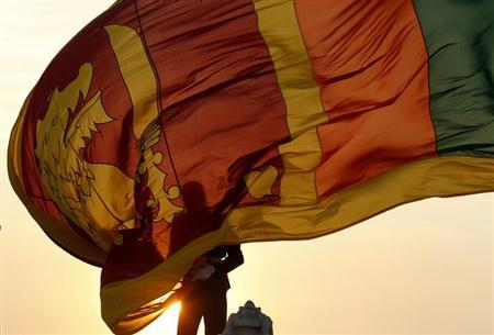 An air force officer holds Sri Lanka's national flag as the sun sets at Galle Face Green in Colombo February 2, 2013. REUTERS/Dinuka Liyanawatte
