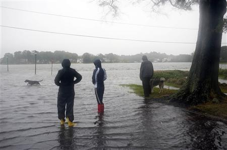 Residents of the Colonial Place neighborhood survey flood waters as heavy rain from Hurricane Sandy floods the Lafayette River in Norfolk, Virginia, in this October 28, 2012 file photo. Built at sea level on reclaimed wetland, Norfolk has faced floods throughout its 400-year history. REUTERS/Rich-Joseph Facun/Files