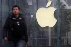 A man walks in front of a company logo outside an Apple store in downtown Shanghai January 24, 2013. . REUTERS/Aly Song