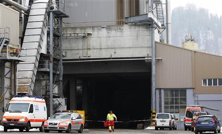 Rescue service members walk in front of the wood processing plant of Kronospan following a shooting in Menznau near Lucerne February 27, 2013. REUTERS/Michael Buholzer